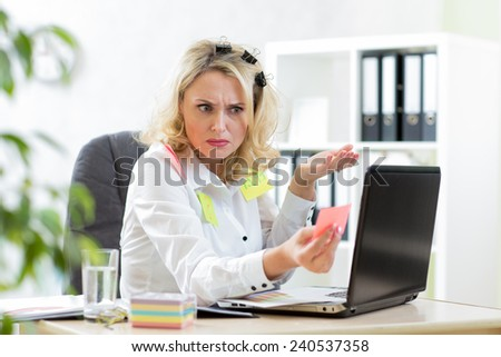 Funny overworked mature businesswoman working in office and looking at stickers reminder notes  - stock photo