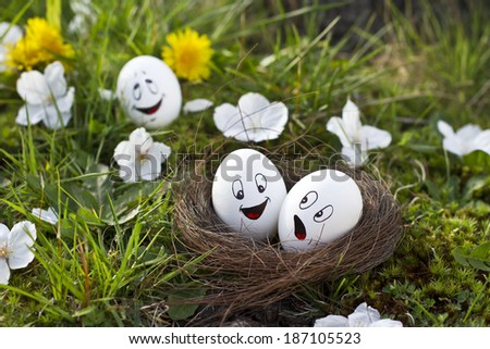 Funny painted eggs in nest on the grass