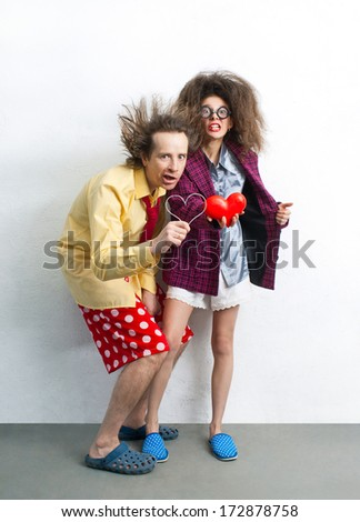 Funny pair of lovers with hearts in the hands - stock photo
