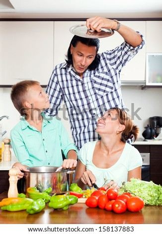 Funny parents with teenager son cooking vegetarian lunch in home kitchen