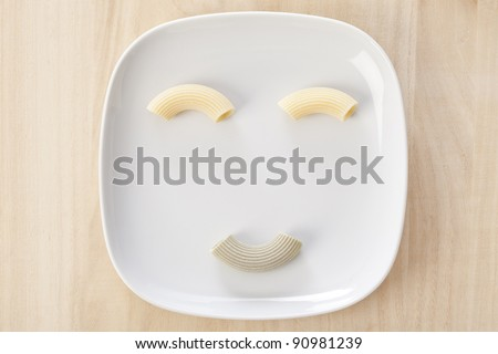 Funny pasta face with italian raw handmade pasta on a white dish.