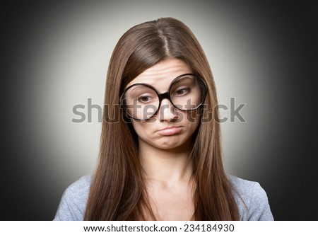 Funny pensive woman in large glasses - stock photo