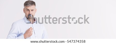 Funny photo of a middle-aged man in a shirt holding a paper moustache