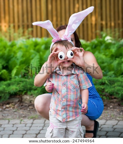 Funny photo of a smiling little boy having fun on Easter wearing bunny ears outside in a garden during the spring season.  His mother holds up silly eyes for him made from eggs.  Part of a series. - stock photo
