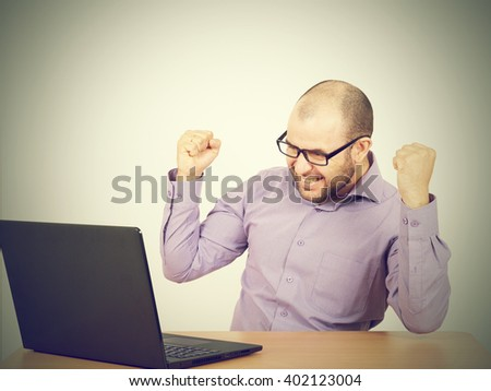 Funny photo of businessman bald with beard wearing shirt and glasses.  angry businessman working with laptop at table. Isolated on gray background  - stock photo