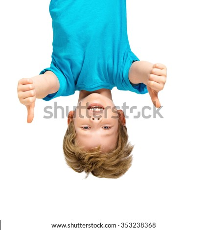 Funny photo of handsome little boy hanging upside down on white background. Boy smiling and showing thumbs up - stock photo