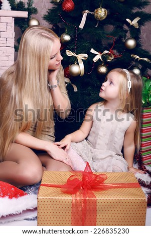 funny photo of little emotional girl sitting with her beautiful mother beside a decorated Christmas tree with presents - stock photo
