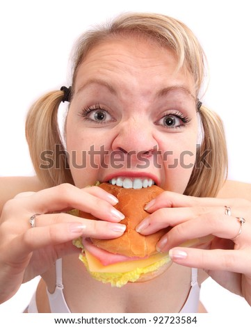 Funny picture of a hungry and angry overweight woman eating tasty sandwich. - stock photo