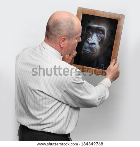 Funny picture of a man and mirror with his monkey face.  - stock photo
