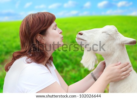 Funny picture of a young farmer woman with his goat. - stock photo