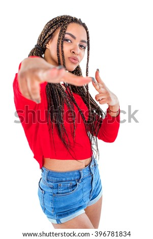 Funny picture of audacious african young woman. Girl with African braids looking at camera and making shooting gesture. Isolated background - stock photo