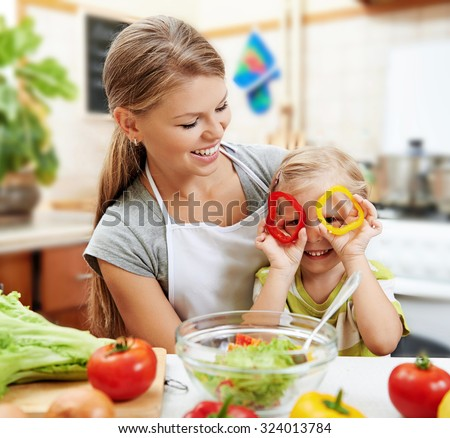 Funny picture of cute little girl holding colorful pepper sitting with her mom at the table in the kitchen.  Young beautiful woman with daughter cooking fresh salad at home.  - stock photo
