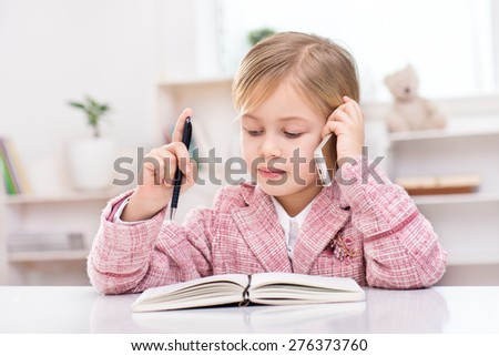 Funny picture of little cute girl playing role of business woman. Girl wearing pink suit. Girl sitting at table with notebook and using phone. Office interior as a background - stock photo