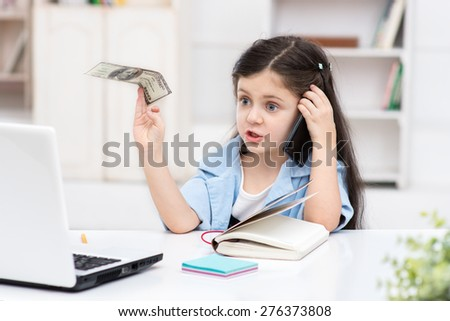 Funny picture of little dark-haired girl playing role of business woman. Girl sitting at table, holding one hundred dollars and using phone. Office interior as a background - stock photo