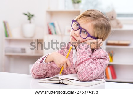 Funny picture of little girl playing role of business woman. Girl wearing pink suit and glasses. Girl thoughtfully sitting at table with notebook and holding pencil. Office interior as a background - stock photo