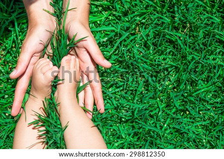 Funny picture of mothers and baby feet. - stock photo