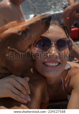 Funny picture of smiling woman in sunglasses with red dachshund - stock photo