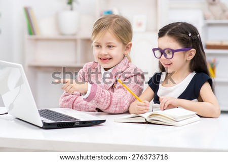 Funny picture of two little cute girls playing role of business women. Girls sitting at table with book and cheerfully looking at laptop. Office interior as a background - stock photo