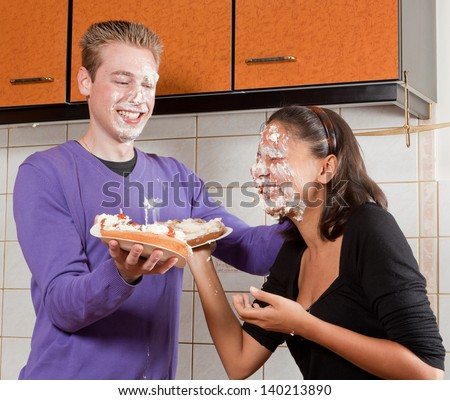 Funny pie fight between a young couple - stock photo
