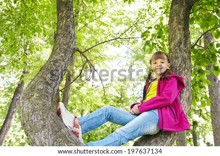 Funny playful little girl sitting on a tree in the park. children outdoors. vacation in the summer park - stock photo