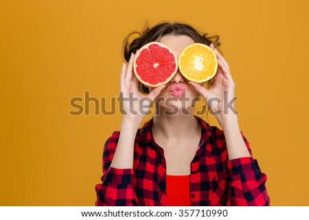 Funny playful young woman in checkered shirt holding halves of citrus fruits against her eyes and making duck face over yellow background - stock photo