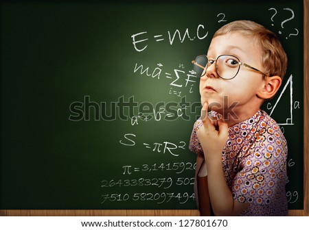 Funny portrait clever pupil boy on school board background - stock photo