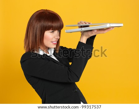 funny portrait of a beautiful, young businesswoman, holding a laptop, peeping to see the screen , on yellow background