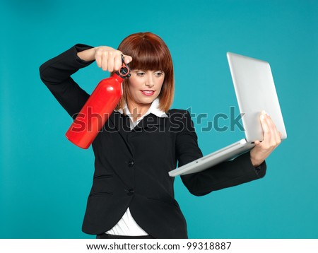 funny portrait of a beautiful, young businesswoman, using a fire extinguisher on her laptop, on blue background