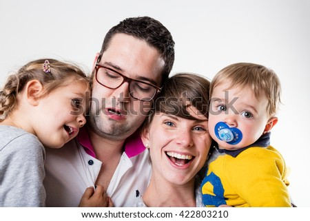 funny portrait of a family in which everyone is laughing but the daughter tugged at his father's collar and he's serious - stock photo