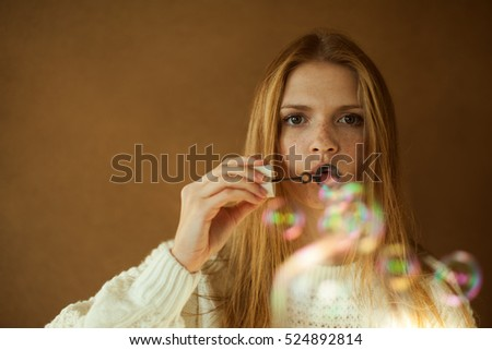 Funny portrait of a fashionable model with long red hair in white sweater blowing party bubbles over wooden background. Hipster style. Daylight. Close up. Copy-space. Studio shot