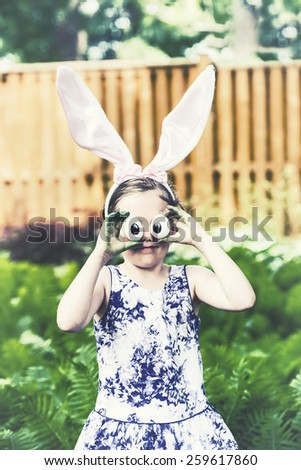 Funny portrait of a girl wearing Easter bunny ears and holding up silly eyes made from eggs outside in a garden during the spring season.  Part of a series.  Filtered for a retro, vintage look. - stock photo