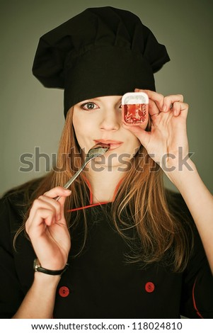 Funny portrait of a joyful lady cook with box of sauce and a metal spoon in the mouth over gray background. studio shot - stock photo