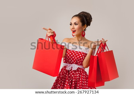Funny portrait of a smiling cute young female model holding many shopping bags in her arms wearing red dress - stock photo