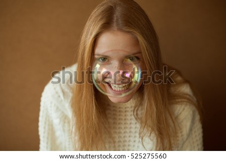 Funny portrait of a smiling fashionable model with long red hair in white sweater laughing behind soap bubble. Hipster style. Daylight. Close up. Copy-space. Studio shot