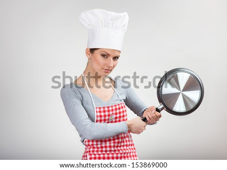 Funny portrait of a woman with the pan on gray background - stock photo