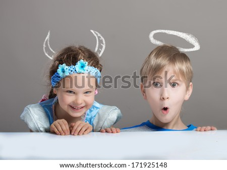 Funny portrait of a 4-year-old girl with painted horns and an older boy with painted halo looking at camera  - stock photo