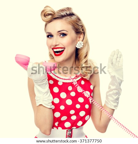 Funny portrait of beautiful smiling woman with phone, dressed in pin-up style red dress in polka dot and white gloves. Caucasian blond model posing in retro fashion and vintage concept studio shoot. - stock photo