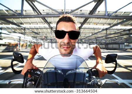 Funny portrait of biker man wearing a white shirt, blue jeans and sunglasses sitting on his classic motorcycle in a empty car parking (wide-angle lens, 14mm, distortion)  - stock photo