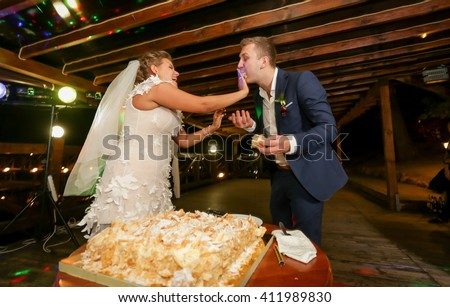 Funny portrait of bride feeding groom with wedding cake at restaurant - stock photo