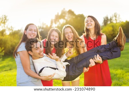 Funny portrait of bridesmaids holding groom on their hands in green sunny park - stock photo