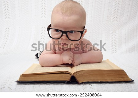 funny portrait of cute little baby as if reading an old book on light background - stock photo
