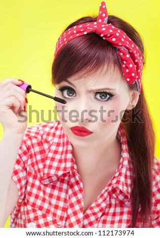 Funny portrait of girl applying mascara - stock photo