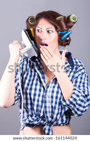 funny portrait of sexy housewife with iron like cell phone - stock photo