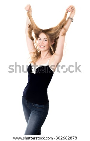 Funny portrait of young attractive cheerful smiling blond Caucasian woman fooling around, having fun messing her long hair with happy expression, studio shot on white background - stock photo