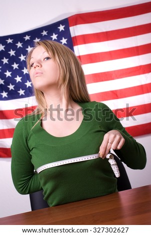 Funny portrait of young beautiful woman with american flag at the background