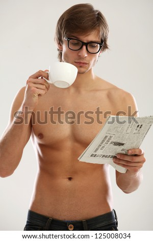 Funny portrait of young naked man with cofee and newspaper isolated over white background - stock photo