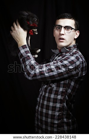 Funny portrait of young nerd with a surprised expresion and a bow holding a black rabbit bunny with a red bow wearing eyeglasses isolated on black background - stock photo