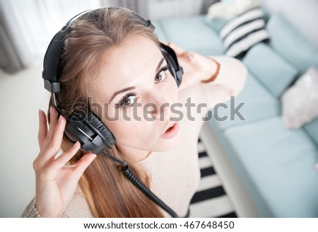 Funny portrait young woman with headphones listening to music at home
