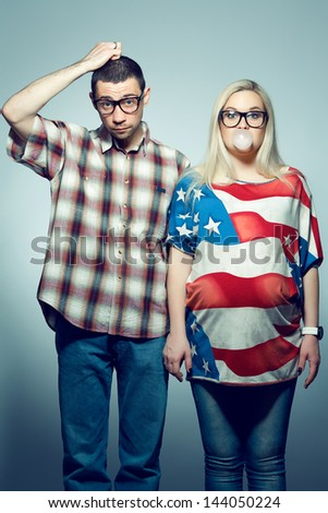 Funny pregnancy concept: portrait of two hipsters (husband and wife) in trendy glasses and clothes posing over gray background. Studio shot - stock photo