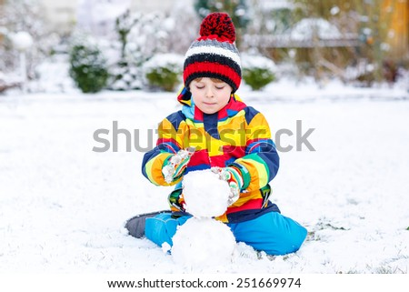 Funny preschool boy in colorful clothes making a snowman, playing and having fun with snow, outdoors  on cold day. Active outoors leisure with children in winter. - stock photo